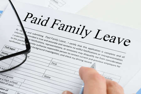 Close-up Of A Persons Hand Holding Pen Over Paid Family Leave Form With Spectacles