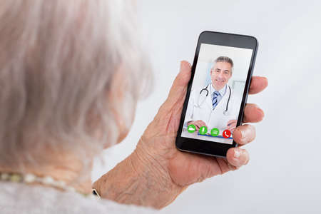 Senior Woman Video Conferencing With Doctor On Smartphone At Home