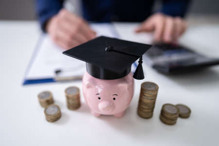 Close-up Of Piggy Bank Wearing Graduation Hat And Stacked Coins In Front Of Businessperson Фото со стока - 137949483