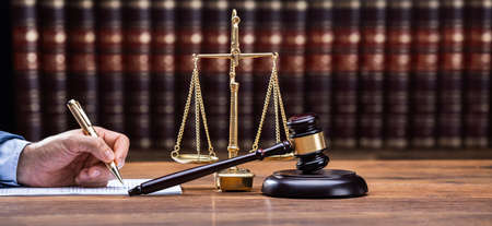 Giudice che scrive su documenti legali alla scrivania