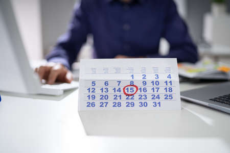 Businessman Marking A Date On Calendar At Workplace