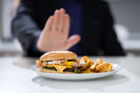 Close-up Of A Man's Hand Refusing To Eat Fest Food Burger