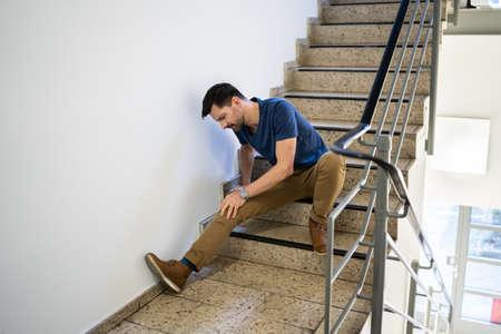Mann sitzt auf Treppe nach Rutsch- und Sturzunfall