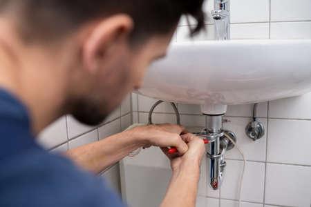 Young Plumber Fixing A Sink In Bathroom Stock fotó