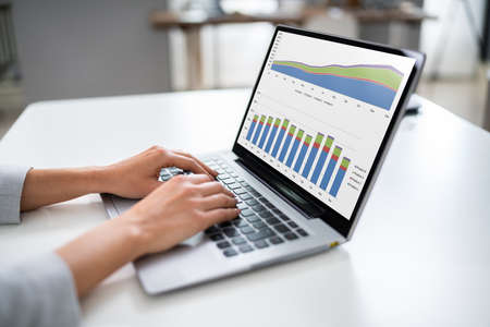 Cropped Image Of Businesswoman Watching Financial Charts On Laptop In Office