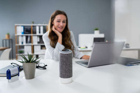 Smiling Woman Listening To Music On Wireless Speaker