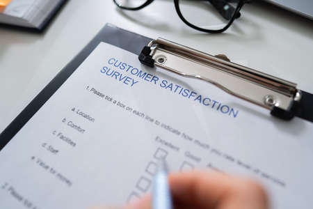 Close-up Of Womans Hand Filling Customer Survey Form