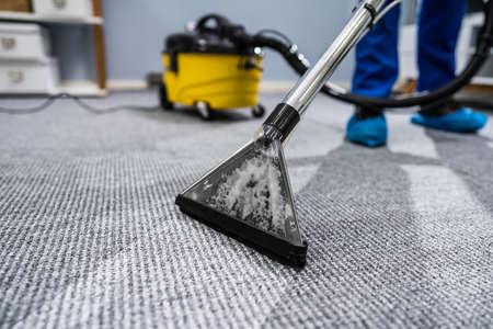 Foto de conserje limpieza de alfombras con aspiradora Foto de archivo