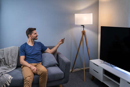 Person Controlling Smart Light With Remote Control Reklamní fotografie