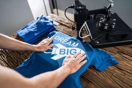 Mann druckt auf T-Shirt in der Werkstatt
