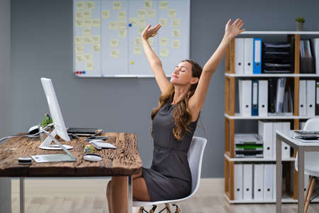 Young Businesswoman Stretching Her Arms At Desk