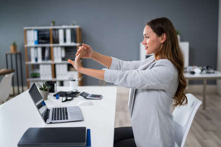 Side View Of A Young Businesswoman Stretching Her Hand In Office