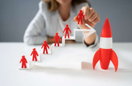 Woman Placing Red Human Figurine Standing On White Increasing Arrow Graph Near Red Rocket