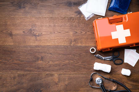 First Aid Kit With Medical Equipment On Wooden Background
