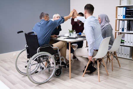 Disabled Businessman Giving High Five To His Smiling Partners In Office