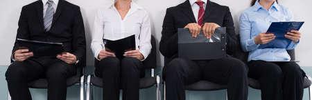 Gruppe von Geschäftsleuten mit Akten, die auf einem Stuhl sitzen und auf ein Vorstellungsgespräch warten Standard-Bild