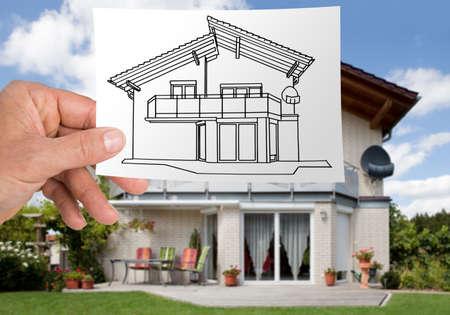 Haus-Illustration vor echtem Haus Standard-Bild