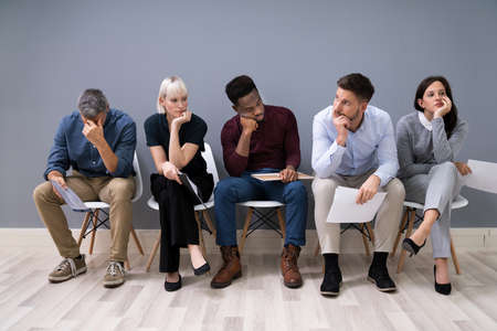 Business People Are Getting Bored While Sitting On Chair Waiting For Job Interview In Office
