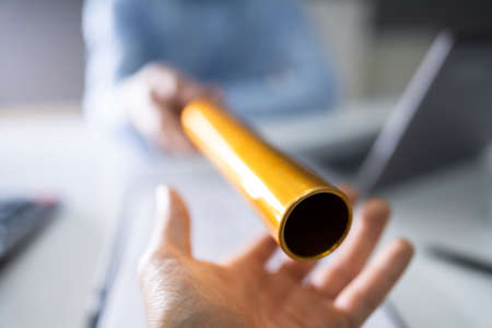Close-up Of A Hand Passing Golden Relay Baton To Businessman