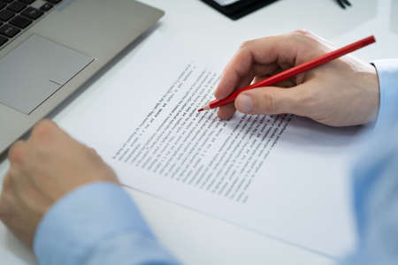 Close-up Of Red Pencil Marking Error During Spellchecking Text On Paper Document
