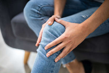 Woman Suffering From Knee Pain Sitting On Sofa