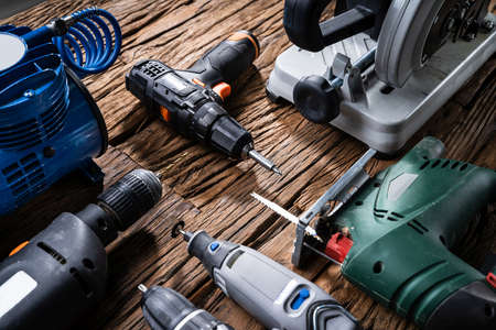Various Power Tools Laying On Wooden Desk