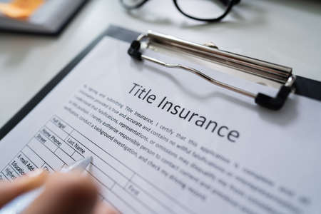 Woman Filling Title Insurance Form Over White Desk Stock Photo