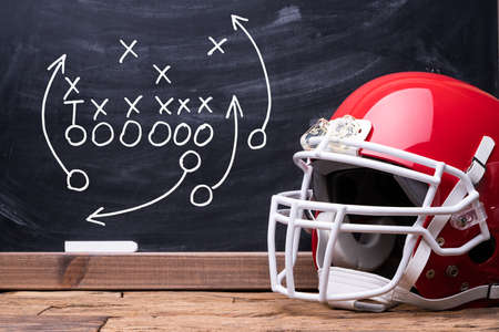 Sport Helmet In Front Of A Chalkboard With Football Play Strategy Stock Photo