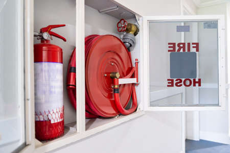 Fire Hose Reel And Fire Extinguisher In Hotel Corridor