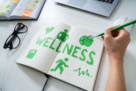 High Angle View Of A Human Hand Drawing Wellness Concept On Notebook