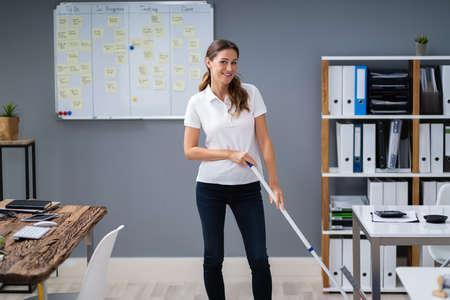 Female Janitor Mopping Floor In Modern Office