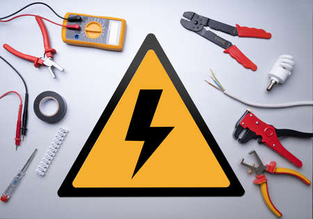 Various Electrician Tools Set Around High Voltage Sign On Gray Background
