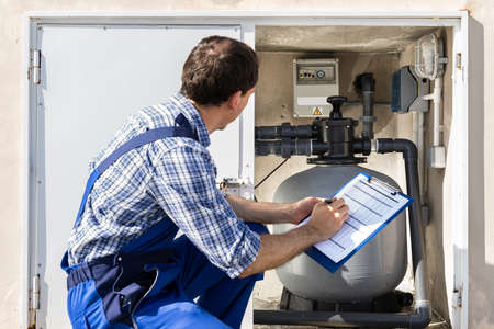 Worker Holding Clipboard Inspecting Water Pump And Pipes Stock Photo