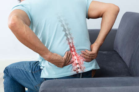Mature Man Sitting On Sofa Suffering From Back Pain Stock Photo