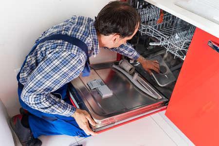 Photo Of Repairman Examining Dishwasher In Kitchen