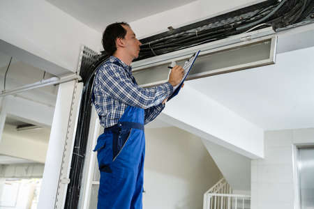 Portrait Of Male Male Electrician Installing Cables Stock Photo