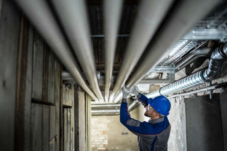 Male Worker Inspecting Water Pipes For Leaks In Basement Stock Photo