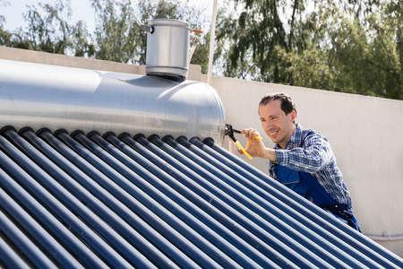 Male Plumber Repairing Solar Energy Electric Boiler Stockfoto