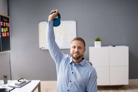 Attractive Businessman Exercising With Kettlebell In Office