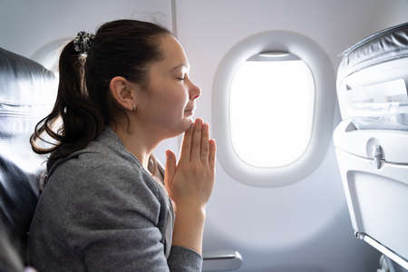 Young Woman Praying For Safe Landing In Airplane