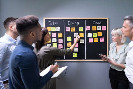 Group Of People Writing On Sticky Notes Attached To Blackboard In Office Stock Photo