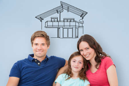 Young Family Sitting On Sofa Thinking Of Getting Their New House