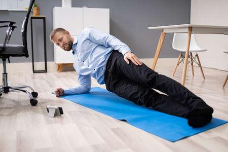 Businessman Exercising Using Smartphone App In Office