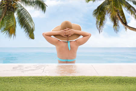 Woman In Infinite Swimming Pool With Palm Trees In Background