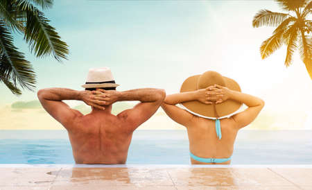 Couple In Infinite Swimming Pool With Palm Trees In Background Stock Photo