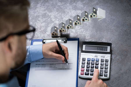 Man Calculating Invoice In Front Of House Models On Increasing Arrow Staircase Stock Photo