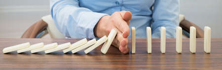 Close-up Of Businessperson Stopping Dominoes Falling On Desk Stock Photo