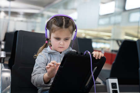 Little Girl In Headphones Playing With Tablet At Airport Stock Photo