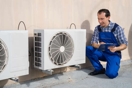 Man Doing Heating, Ventilation, And Air Conditioning Inspection Stock Photo