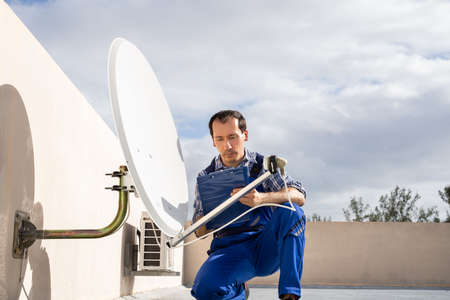 Young African Man In Uniform Fitting TV Satellite Dish On Roof